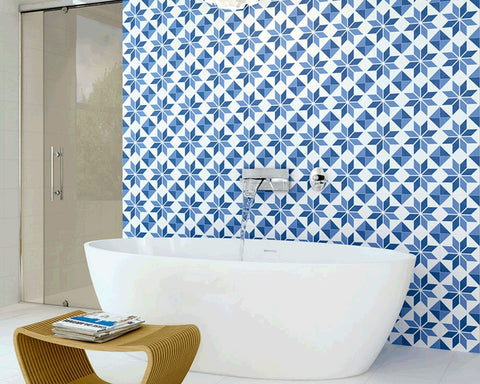 A white bathroom with one wall tiled with blue Morroccan tiles