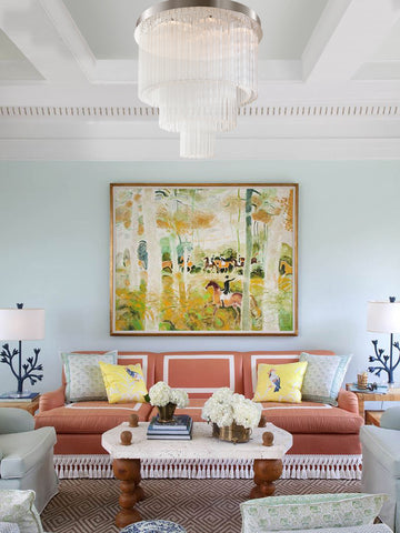 Jade chandelier y The Vault hangs above a colorful coral pink sofa and a chartreuse painting.