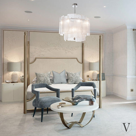 Galjour Chandelier by The Vault hangs above a large four-post bed