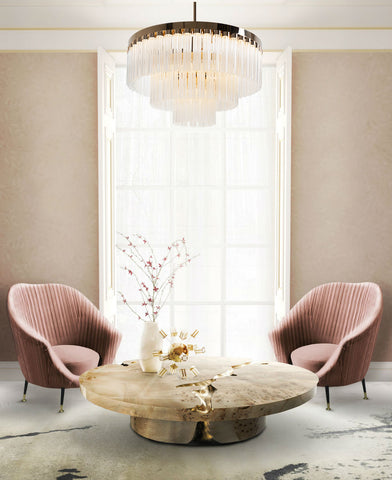 Wallace Chandelier by The Vault hangs above a rustic wood coffee table, with two dusty pink antique chairs.