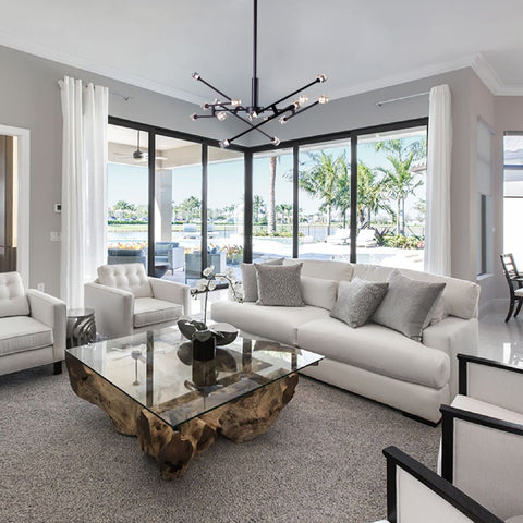 Triton Chandelier shown installed in a living room over a coffee table
