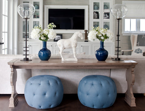 Blue tufted ottomans and a horse sculpture