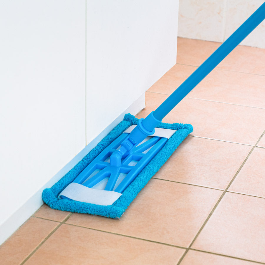 Sweep and Swipe mop cleaning a tiled floor with the head flush against a baseboard
