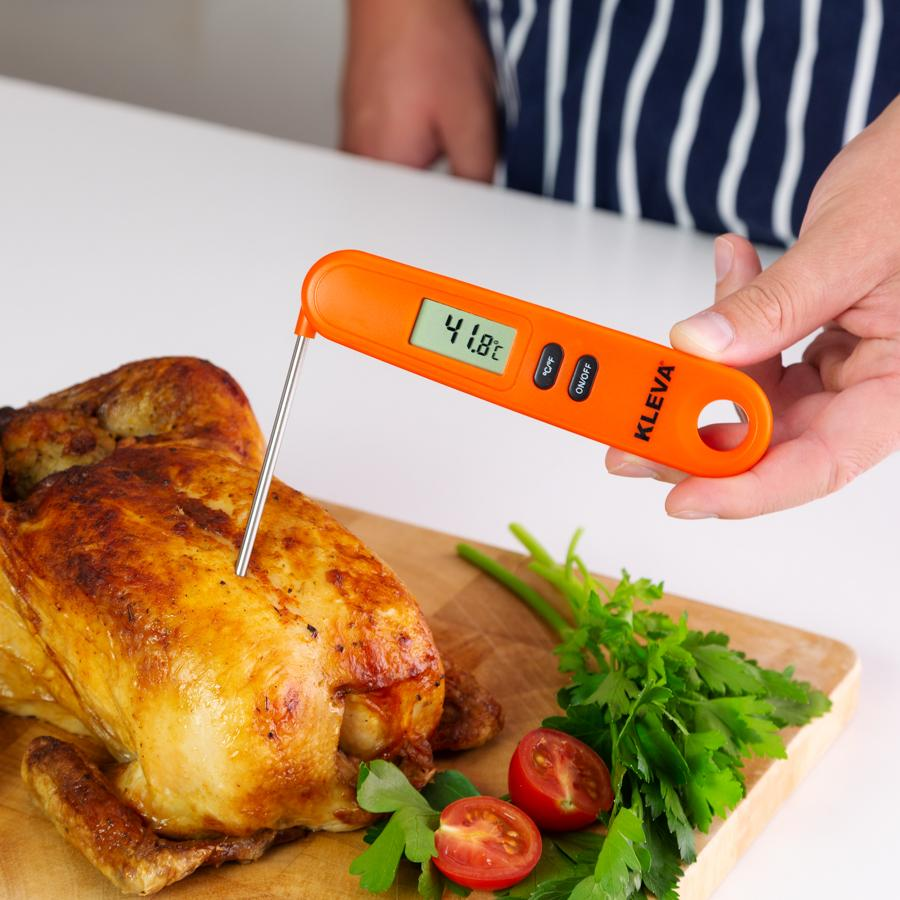 Person using an orange Meat Thermometer on a roast chicken on a 90 degree angle.