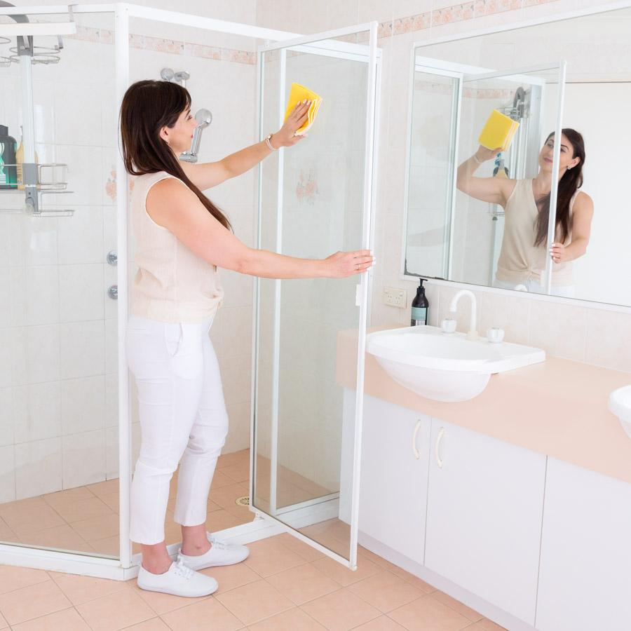 Woman using a yellow microfibre cloth to clean a glass shower door