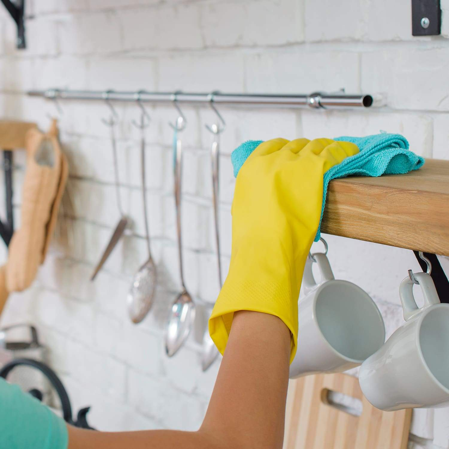 Person wearing a glove and cleaning a kitchen cupboard with the blue microfibre cloth