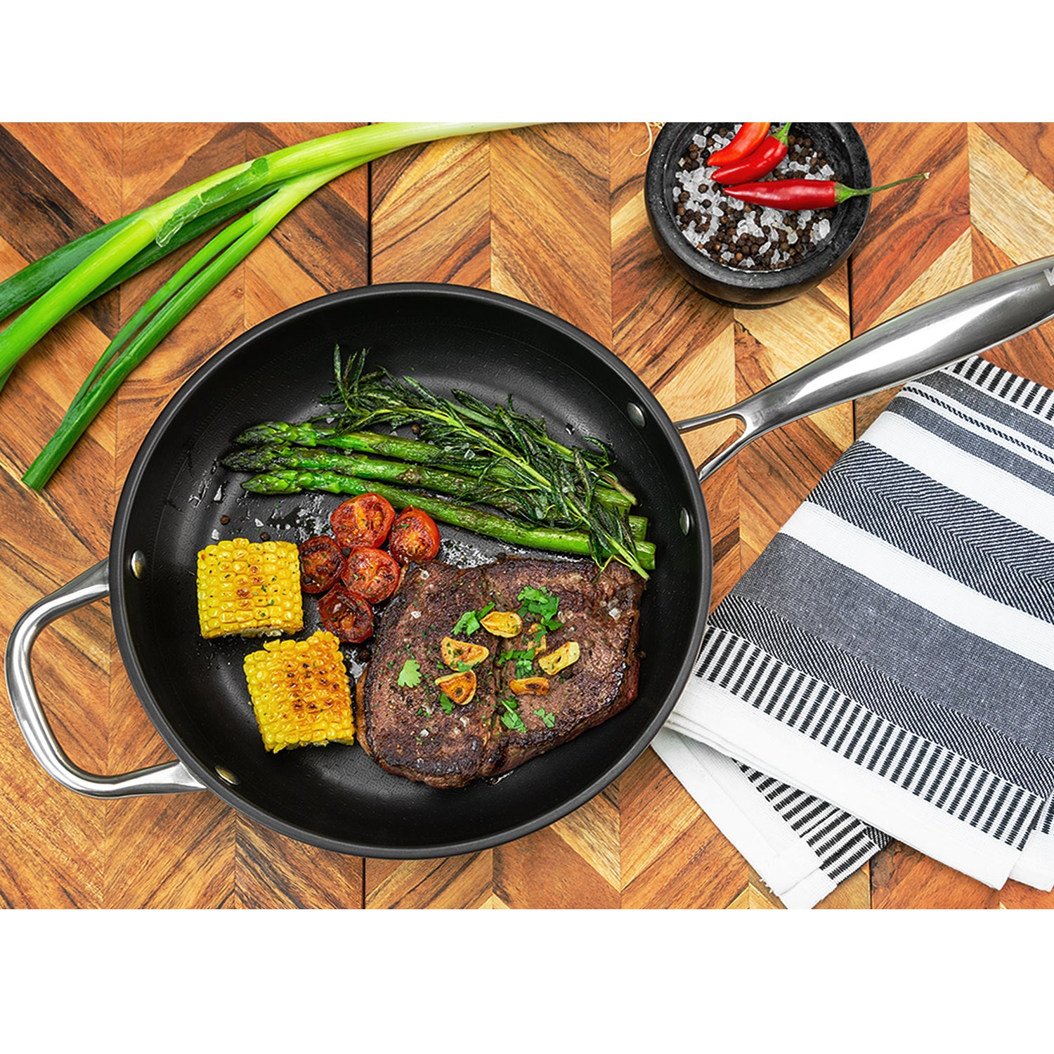Perfect Pro Pan with cooked steak and vegetables on a table.
