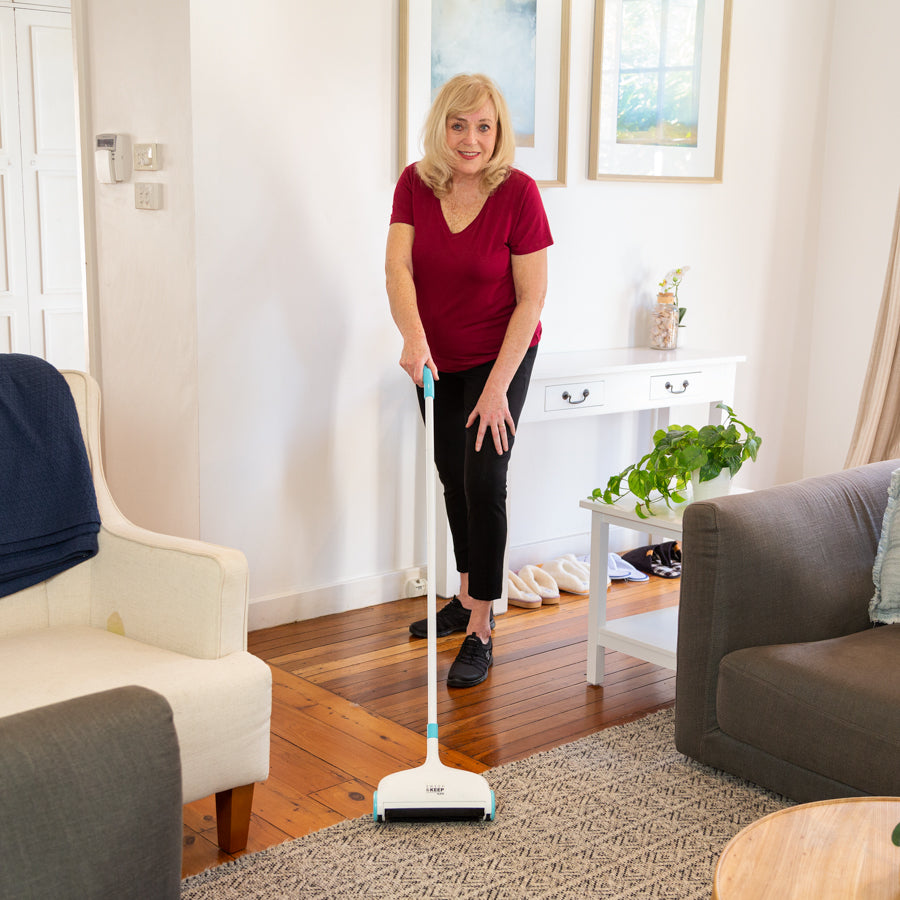 Woman in a living room using the Sweep and Keep on a rug