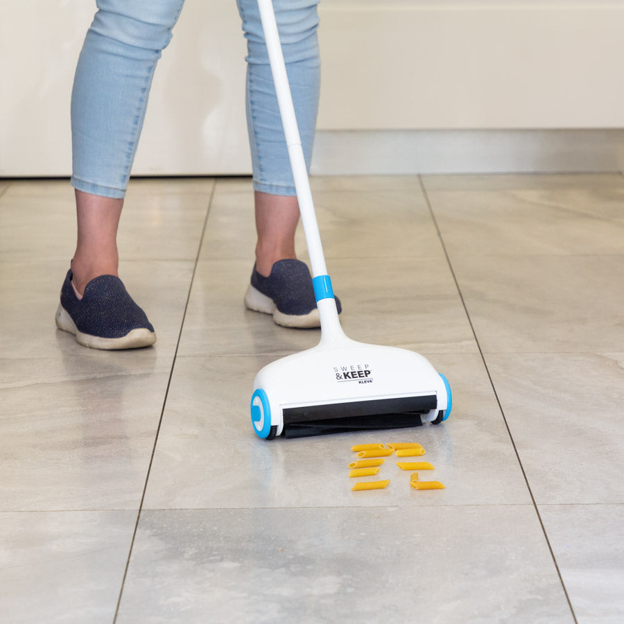 Person using the Sweep and Keep to collect spilled pasta off a Tiled Floor