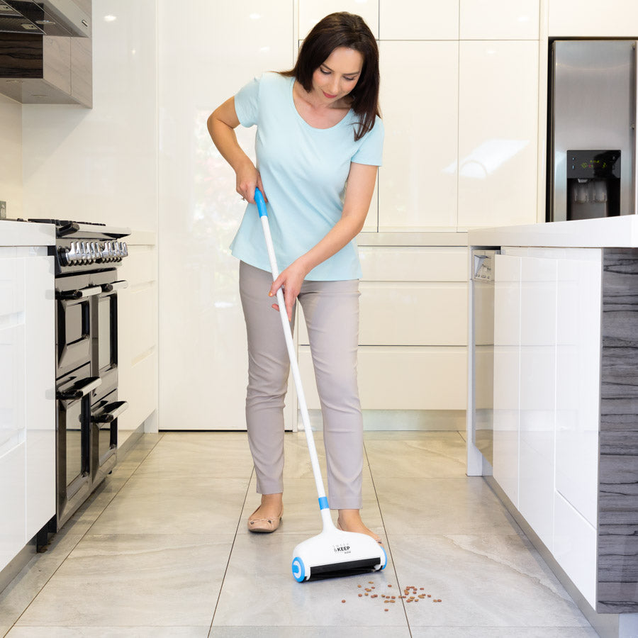 Woman in a tiled kitchen cleaning up dog food with the Sweep and Keep