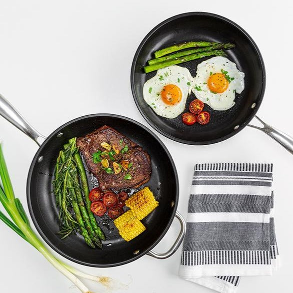 Two Perfect Pro Pans with cooked vegetables, meat and eggs on a white background