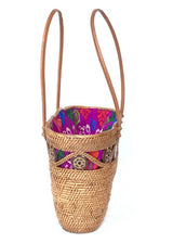 The Laura tote is handwoven Bali basket purse lined in Batik pattern side view.
