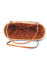 The Laura tote is handwoven Bali basket purse lined in solid brown fabric inside view.