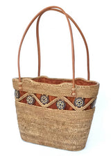 The Laura tote is handwoven Bali basket purse lined in solid brown fabric left angle.