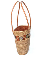 The Laura tote is handwoven Bali basket purse lined in solid brown fabric side view.