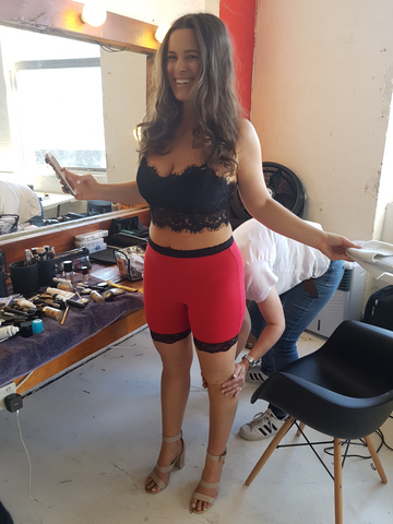 Model wearing red anti-chafe shorts whilst getting ready for photoshoot