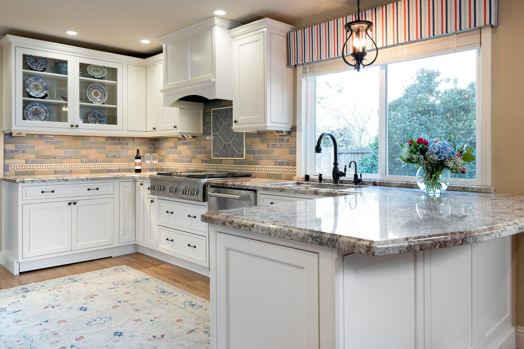 Concord California Kitchen Remodel by Interior Designer Jackie Lopey with Crystal Cabinet Works white painted inset cabinets, ogee ceramic tile inset over range top, wood floors, handmade ceramic tile backsplash, Cambria quartz countertops and Legrand Adorne undercabinet lighting system