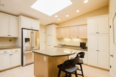 After Photo of Remodeled Kitchen with White Painted Cabinets, Contrasting Island, Black Counter Stools & Quartz Countertops