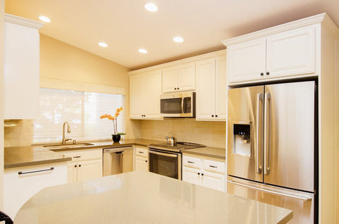 After Photo of Remodeled Kitchen with White Painted Cabinets, Stainless Steel Appliances and Quartz Countertops
