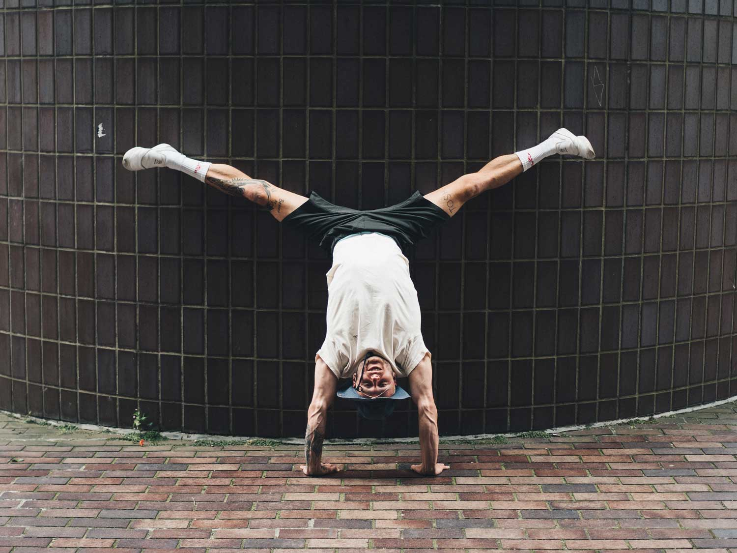 Man doing a straddle handstand against a wall