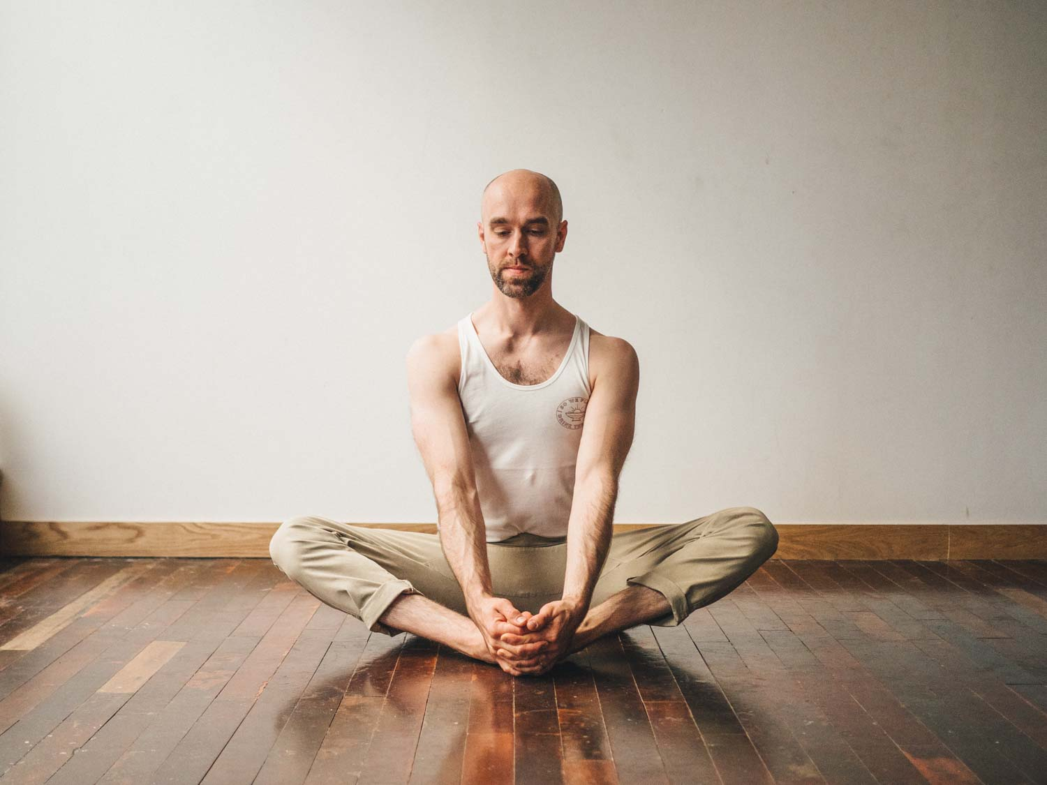 Man doing bound angle pose or Baddha Konasana in yoga studio