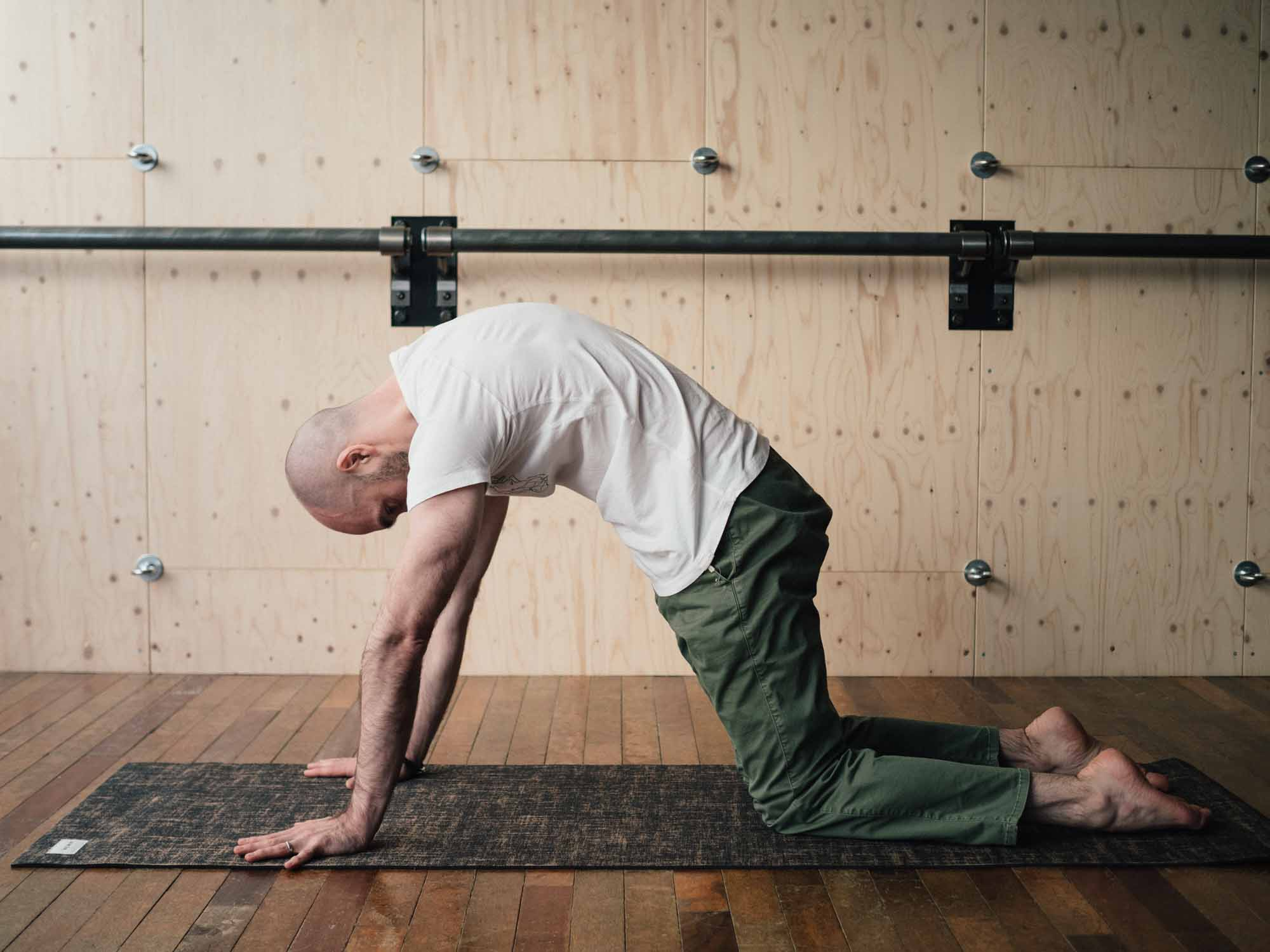 Man doing Cat pose in a yoga studio