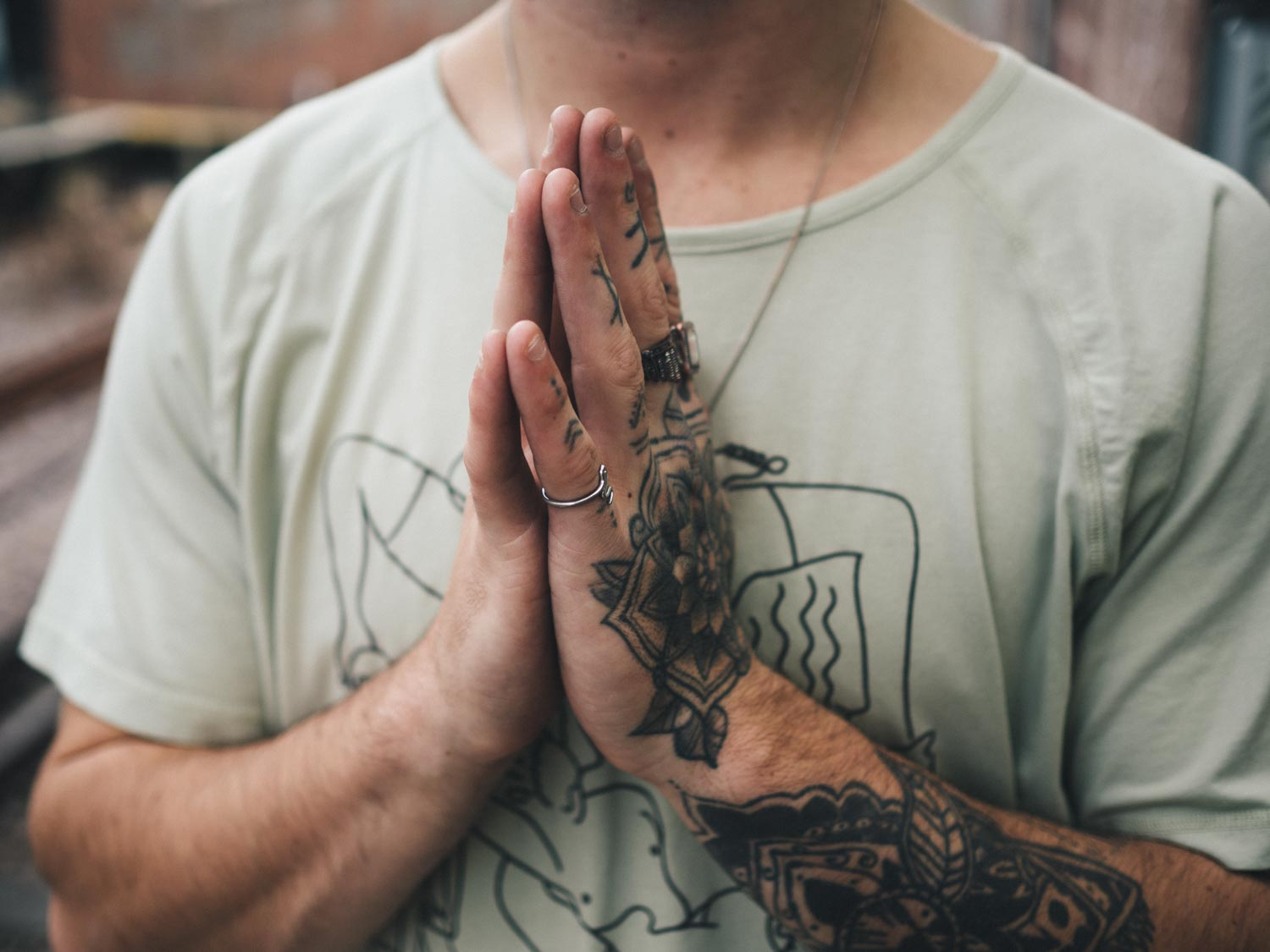 Man with hands in Anjali mudra or prayer hands wearing So We Flow...