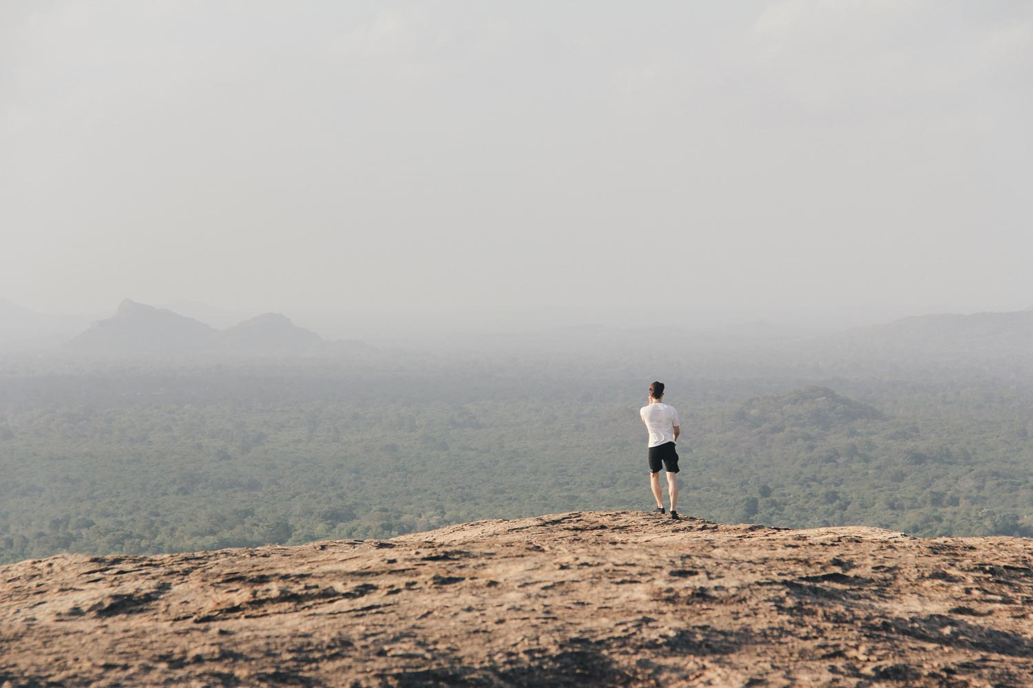 so we flow... Man standing on mountain in white t-shirt