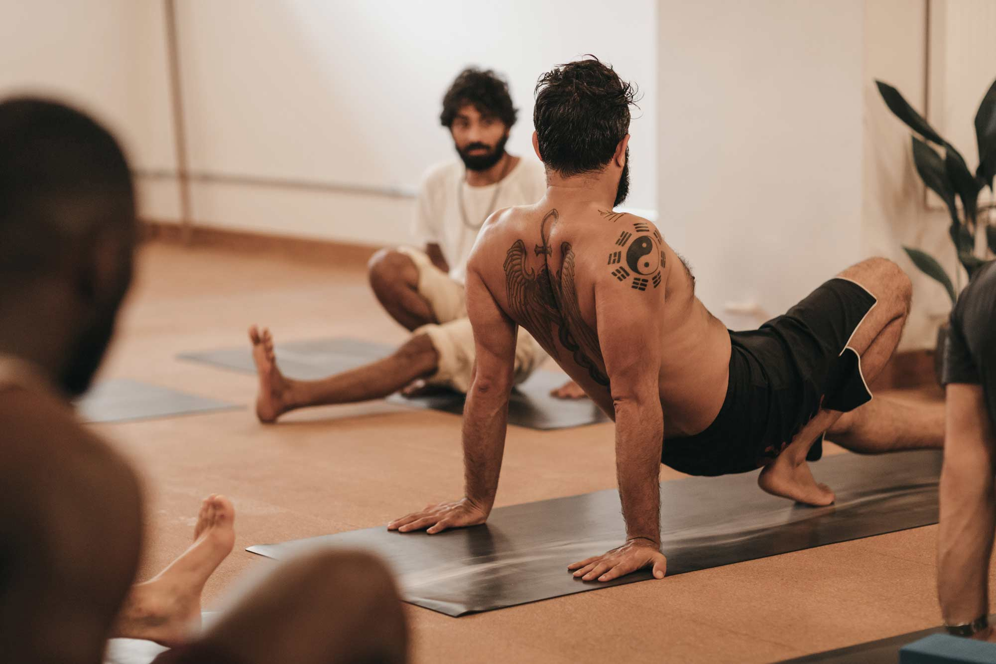 Yoga teacher teaching a male focused yoga class