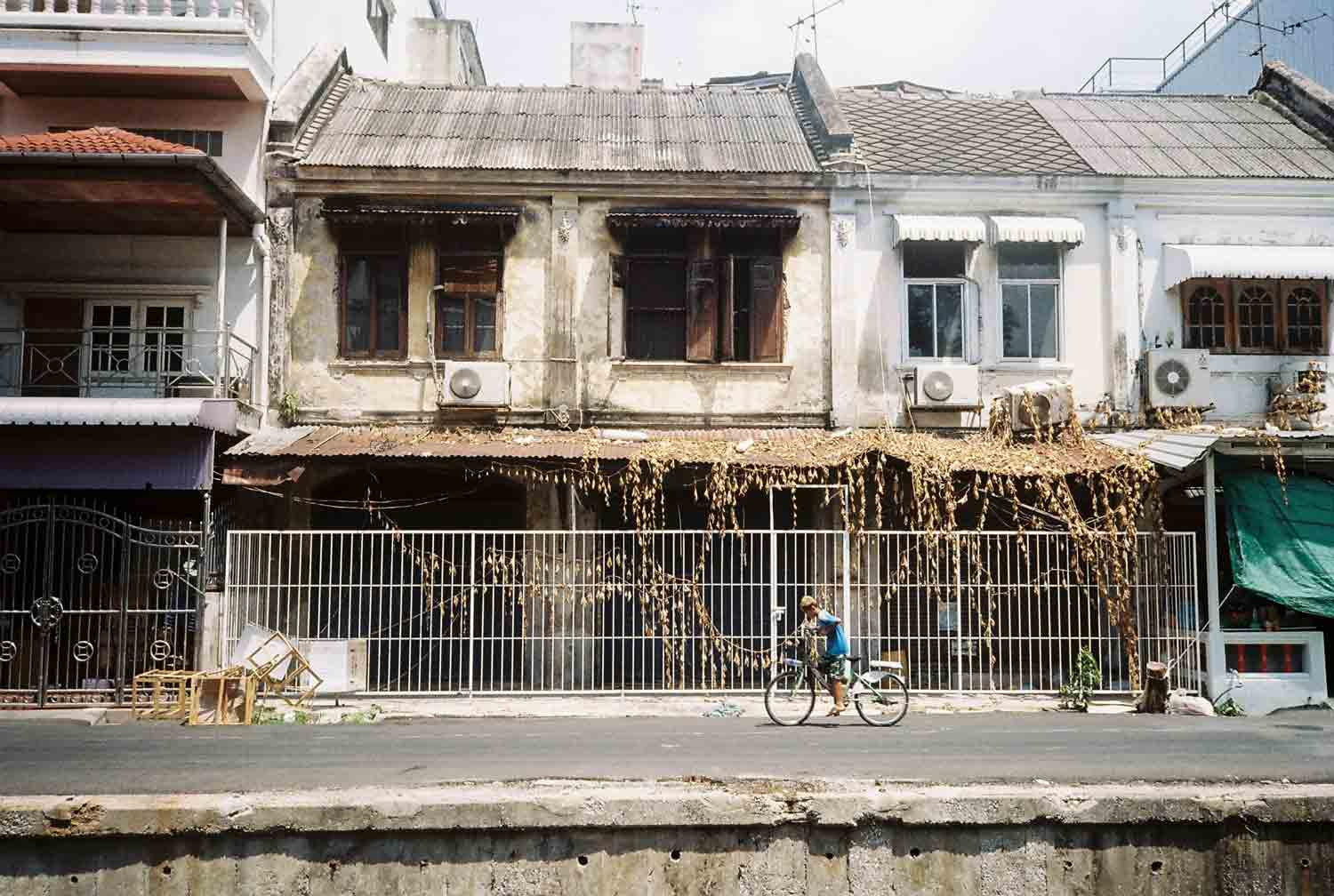 Boy on a bicycle in Bangkok in front of houses