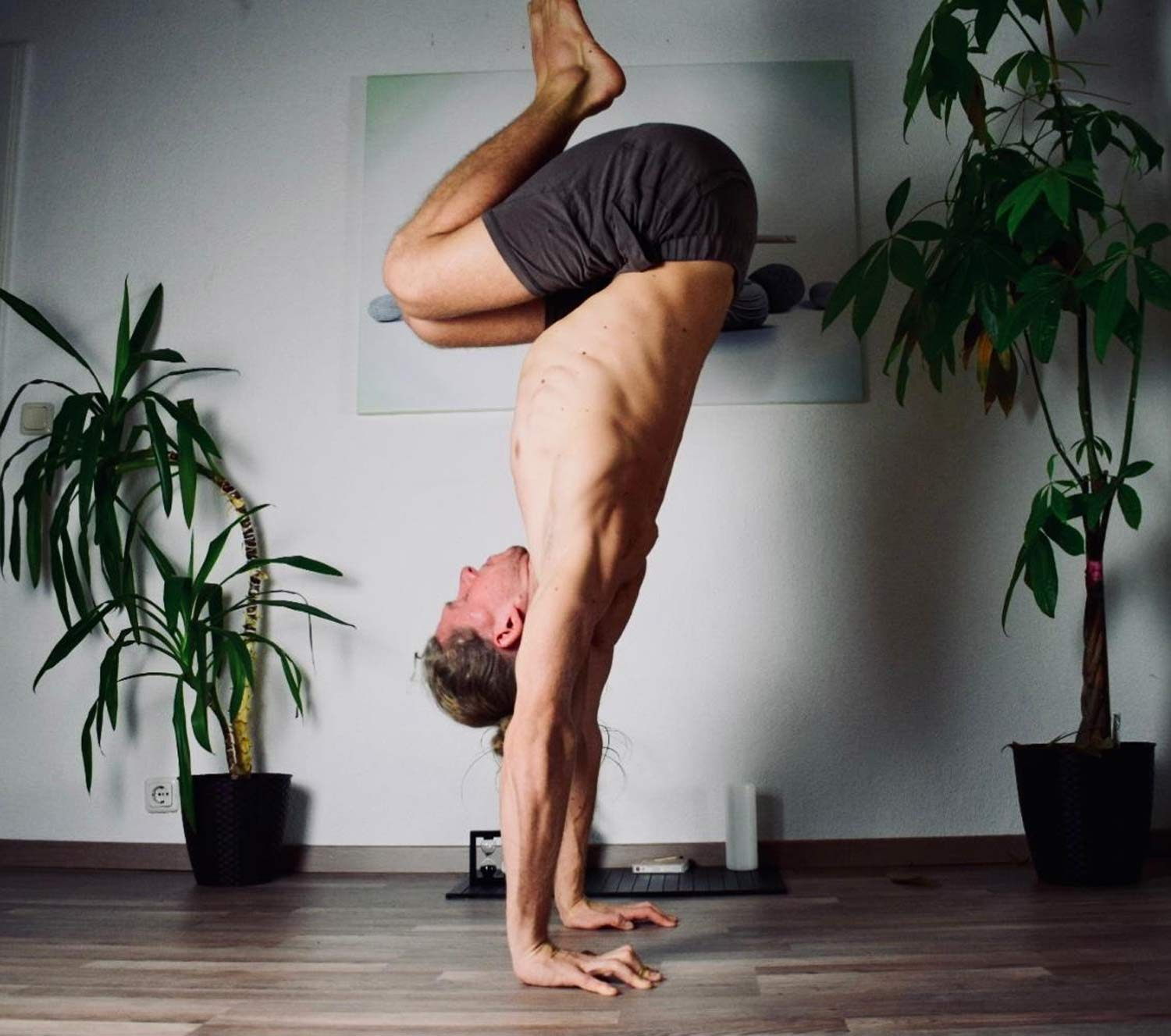 Man doing a tucked handstand wearing So We Flow...