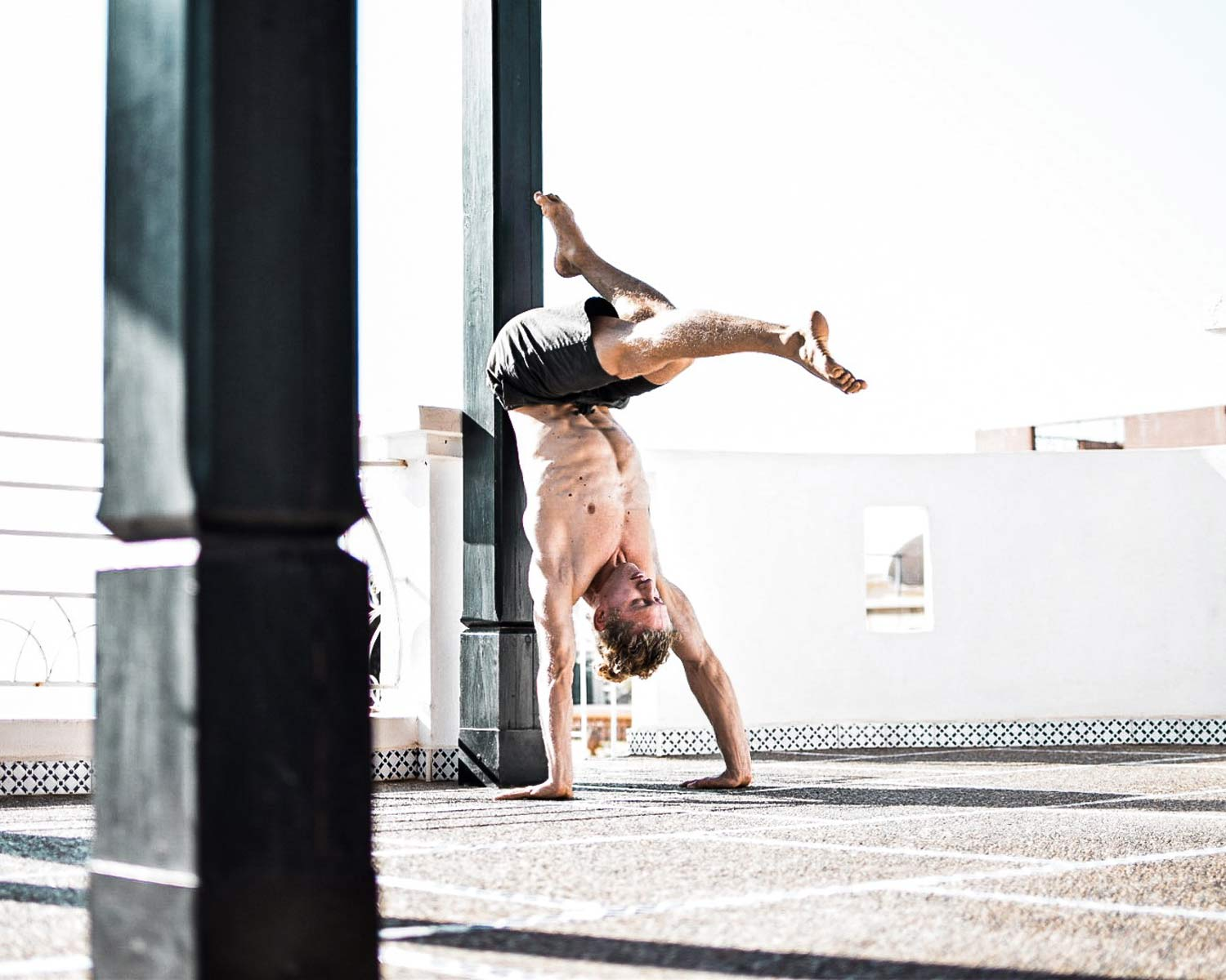 Man doing a negative press handstand wearing So We Flow...