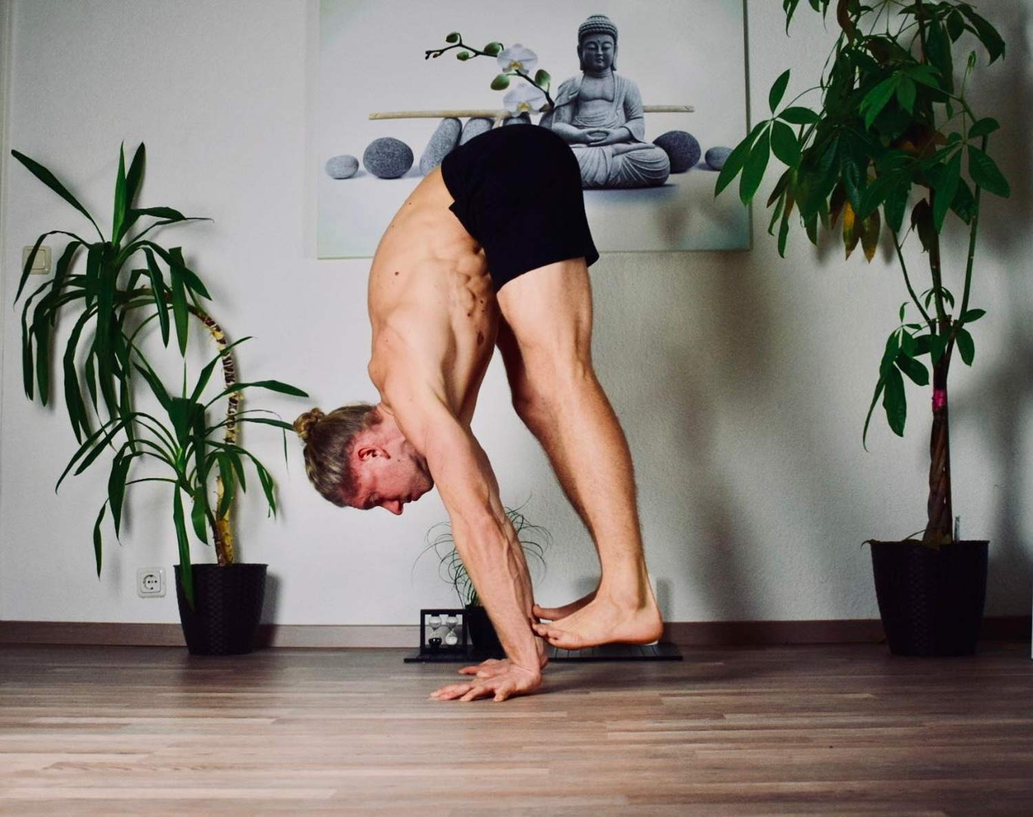 Man showing the technique of a press handstand wearing So We Flow...