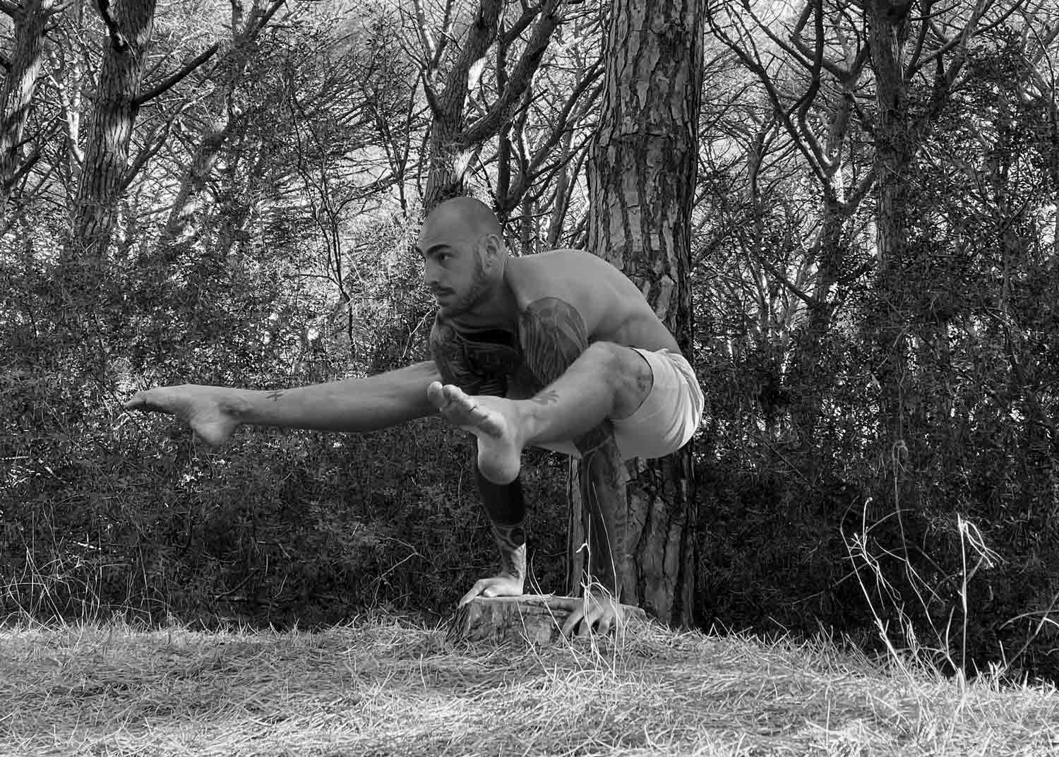 Miles Mortensen doing an arm balance in a forest wearing So We Flow...
