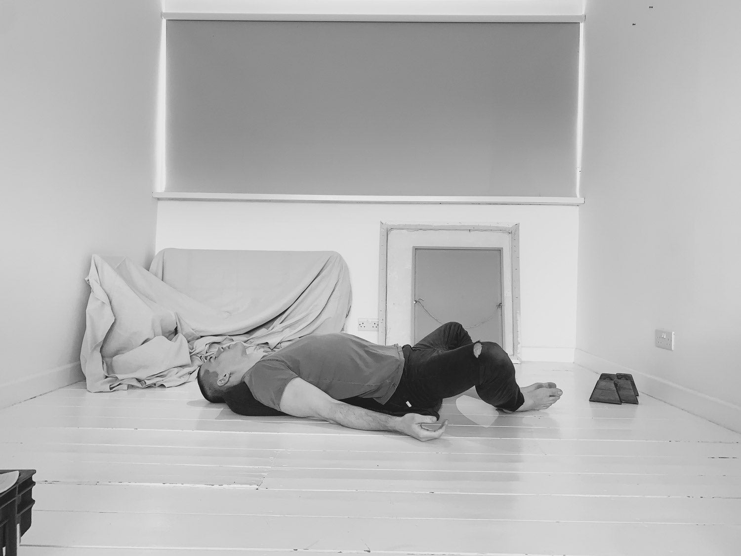 Man doing Reclined Supported Butterfly Yin yoga pose wearing So We Flow...