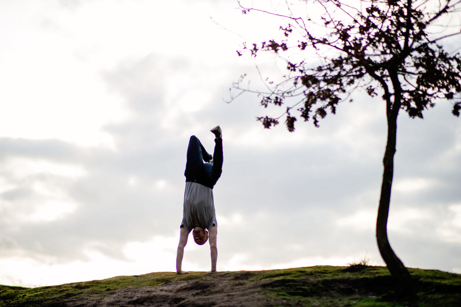 Man doing a handstand wearing So We Flow...