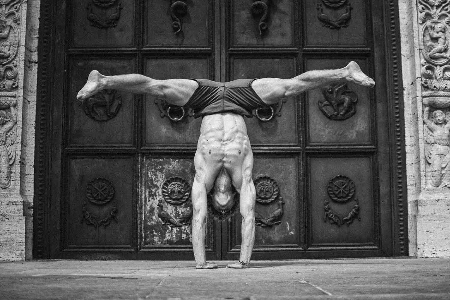 Theo doing a straddle handstand to show overhead mobility wearing So We Flow...