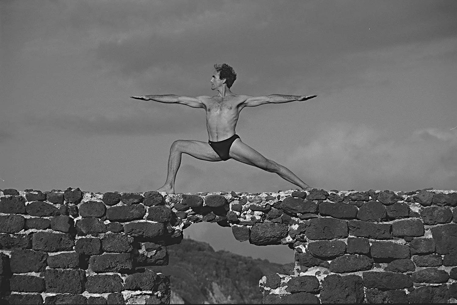 David Swenson in Warrior Two Pose on a wall