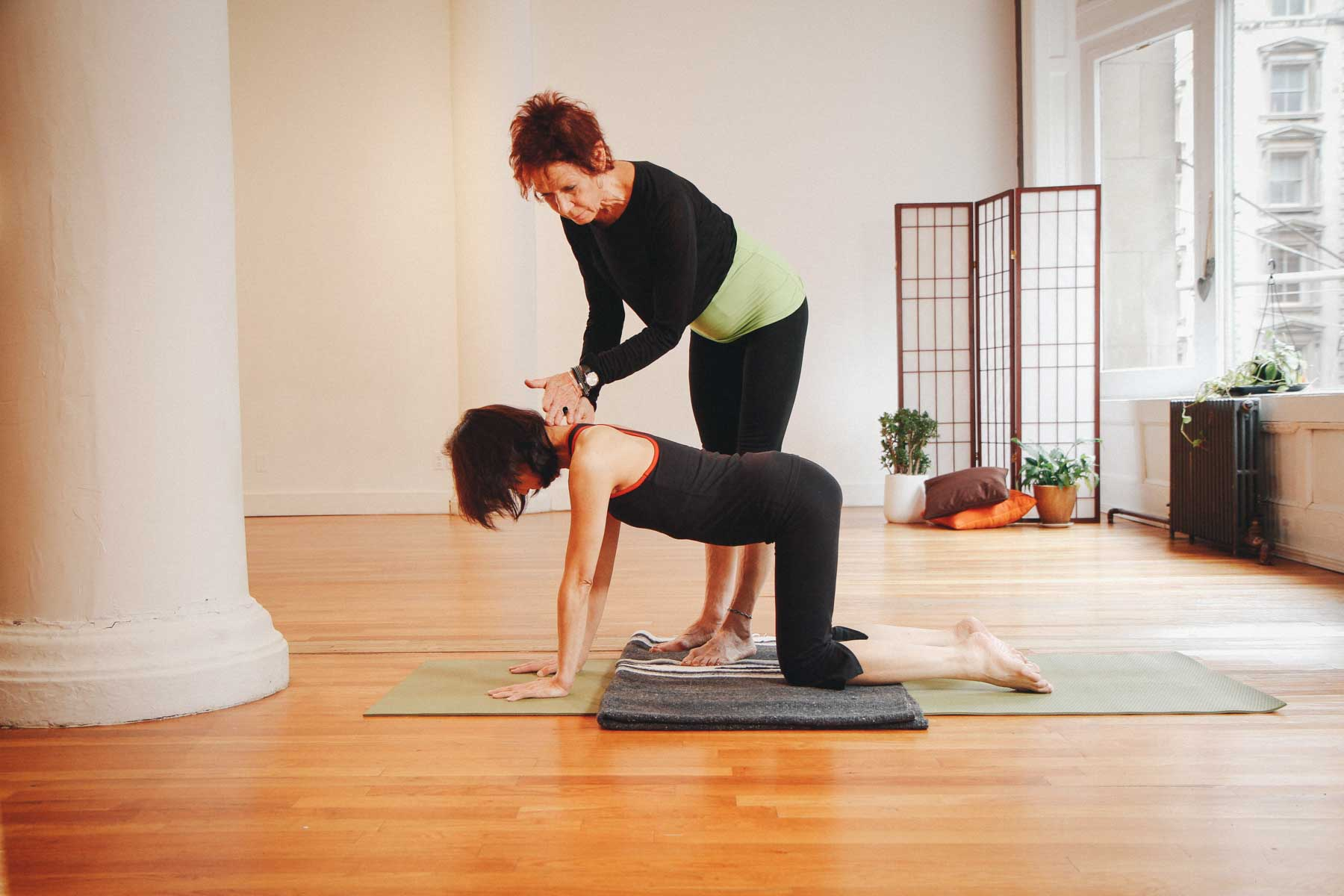 Female yoga teacher assisting female yoga student in a kneeling yoga pose