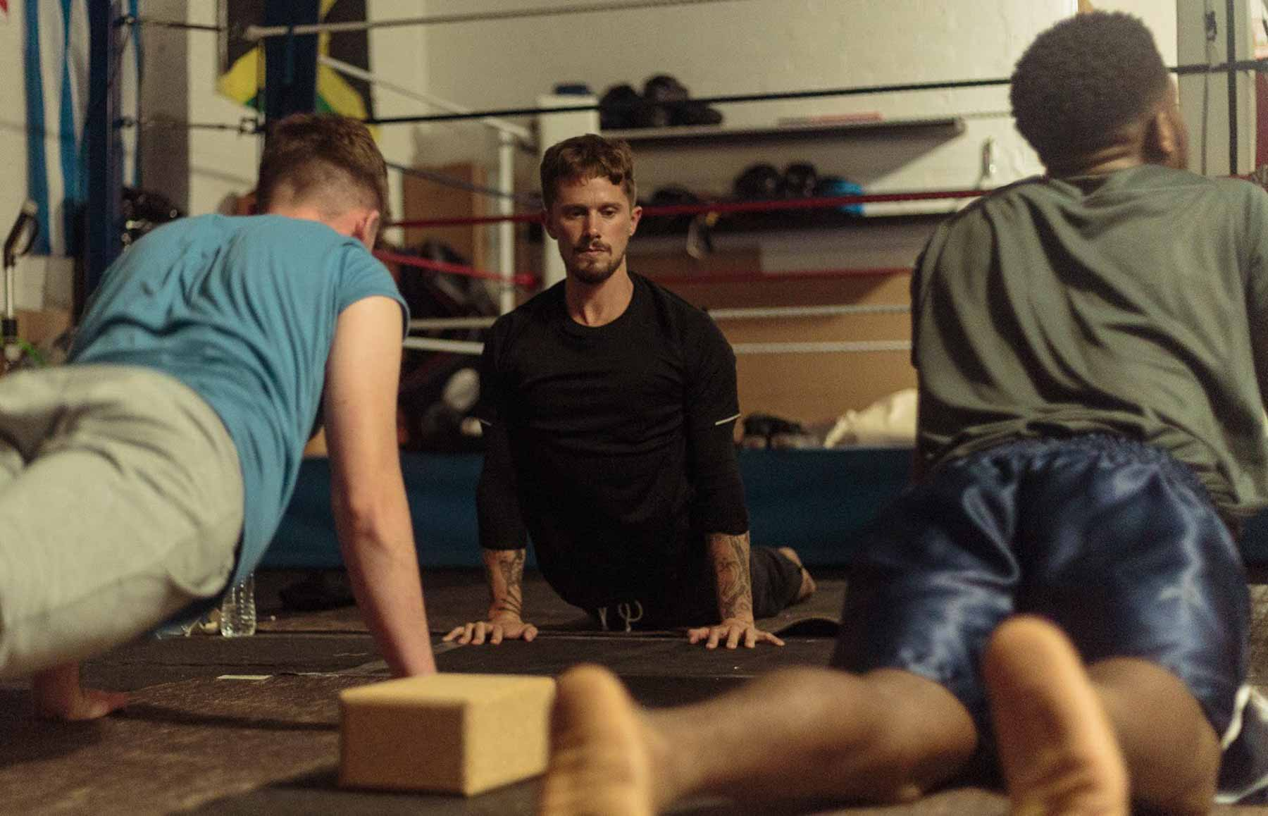 Three men practicing yoga in a boxing gym