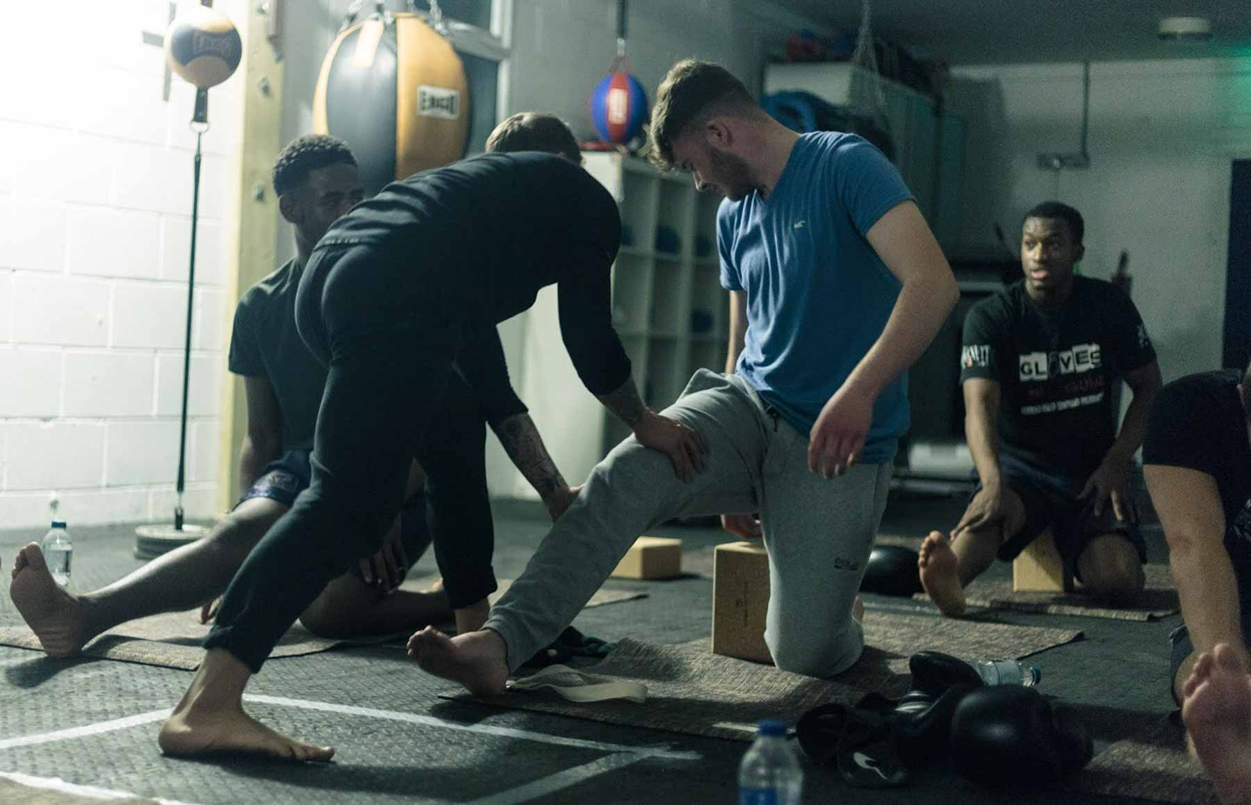 Man assisting a yoga student in a boxing gym