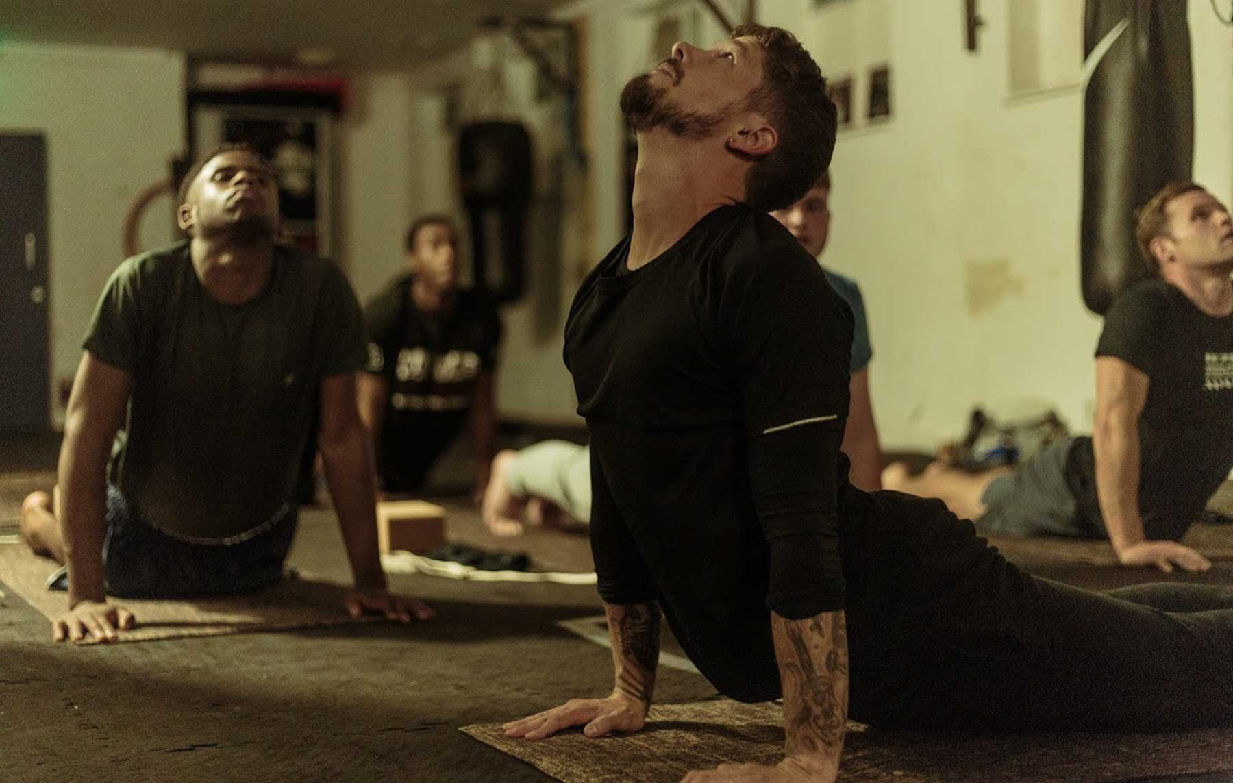 Yoga teaching showing Upward Dog pose to his students