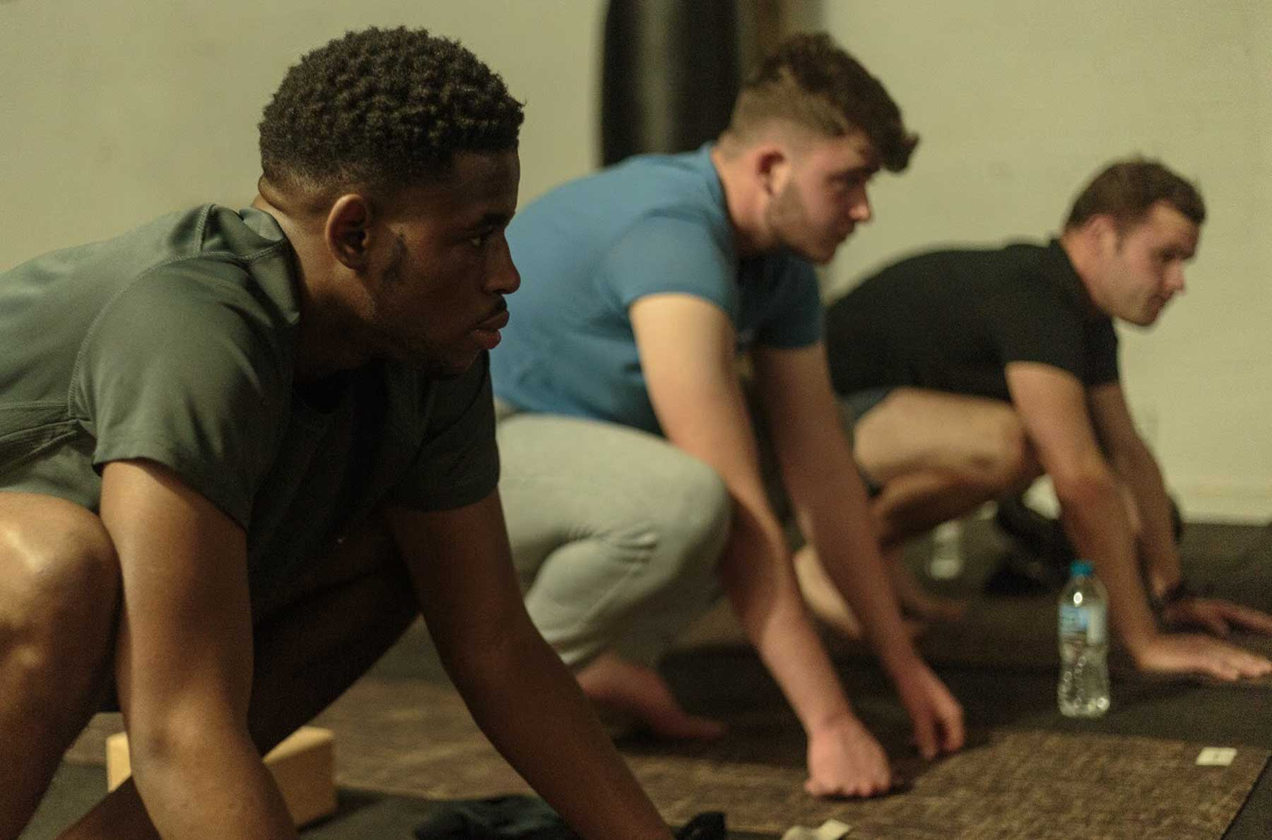 Three young men doing yoga squat