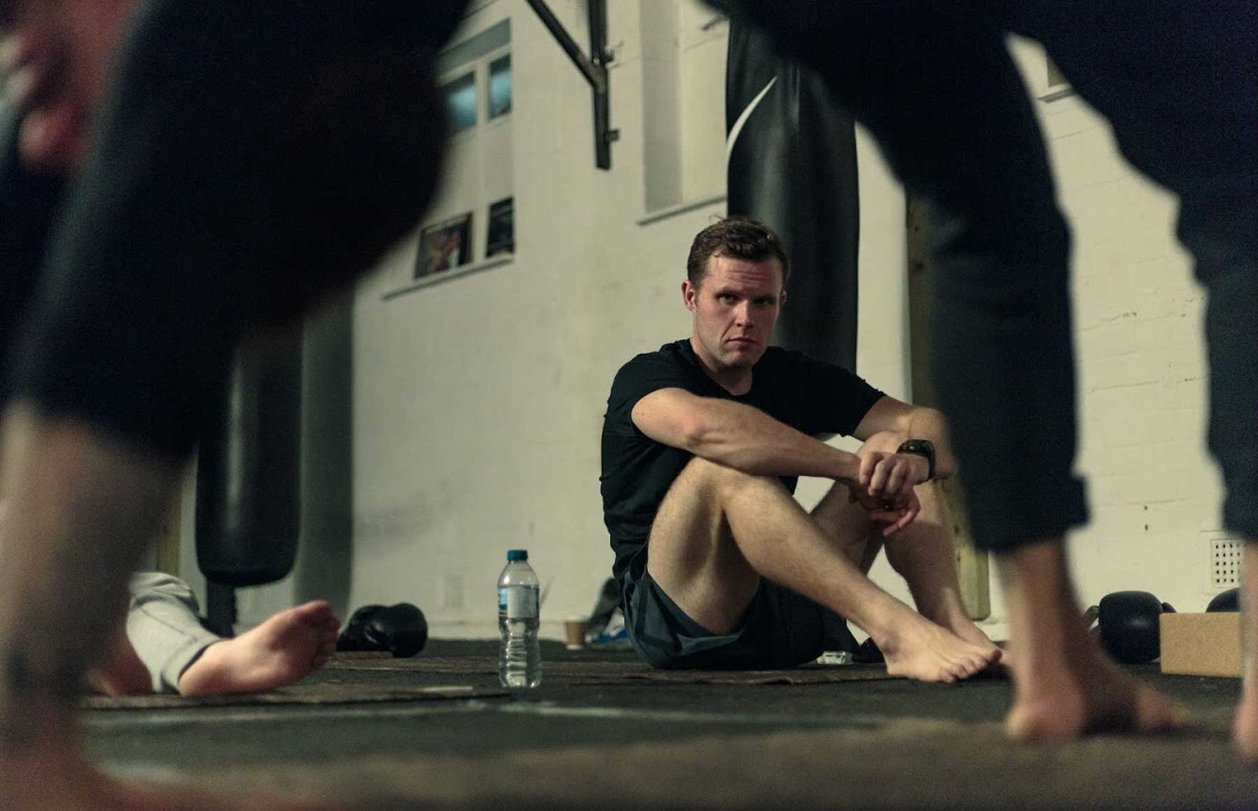 Man observing a yoga teacher in a boxing gym