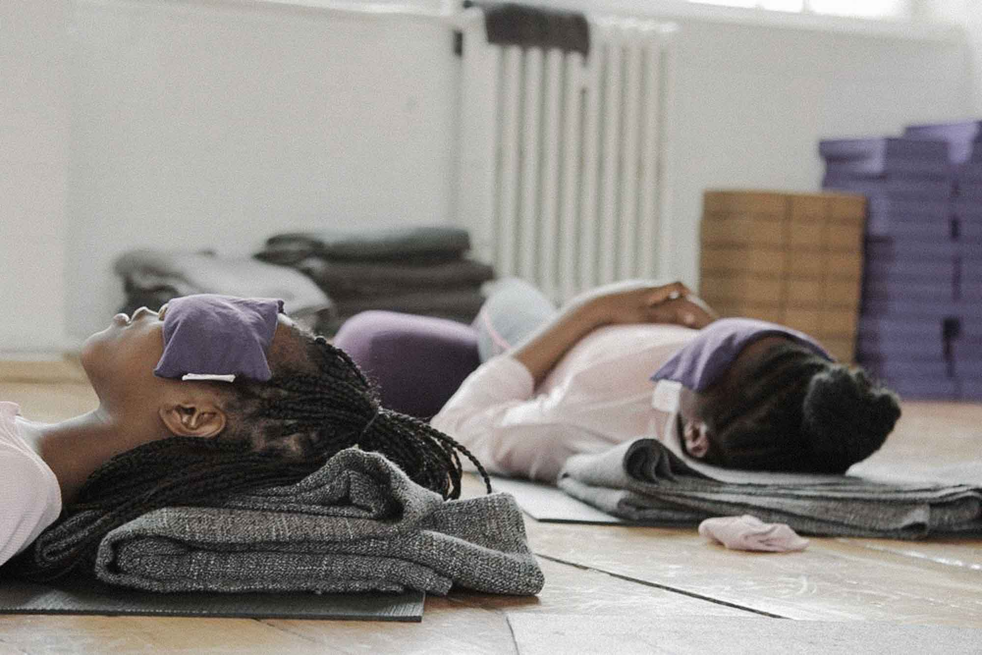 Two girls lying in relaxation during a yoga class