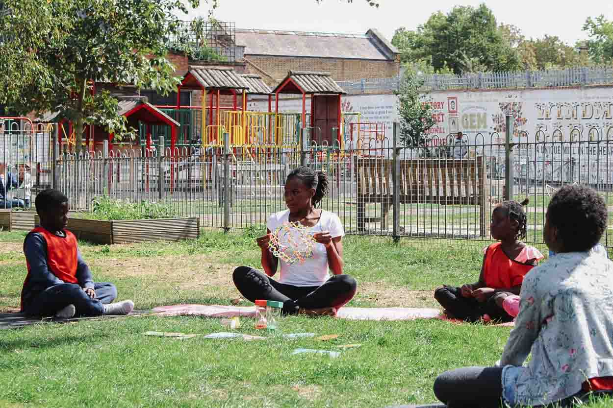Amani Eke from Project Yogi teaching yoga to school children outdoors