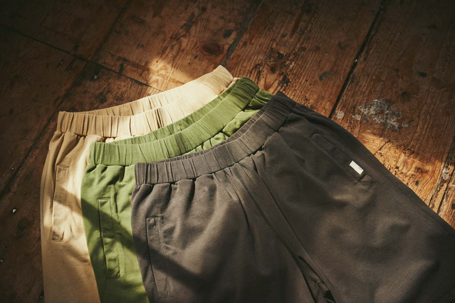 so we flow... Jersey Longs Men's Yoga Pants in Sand, Olive and Grit on a wooden floor