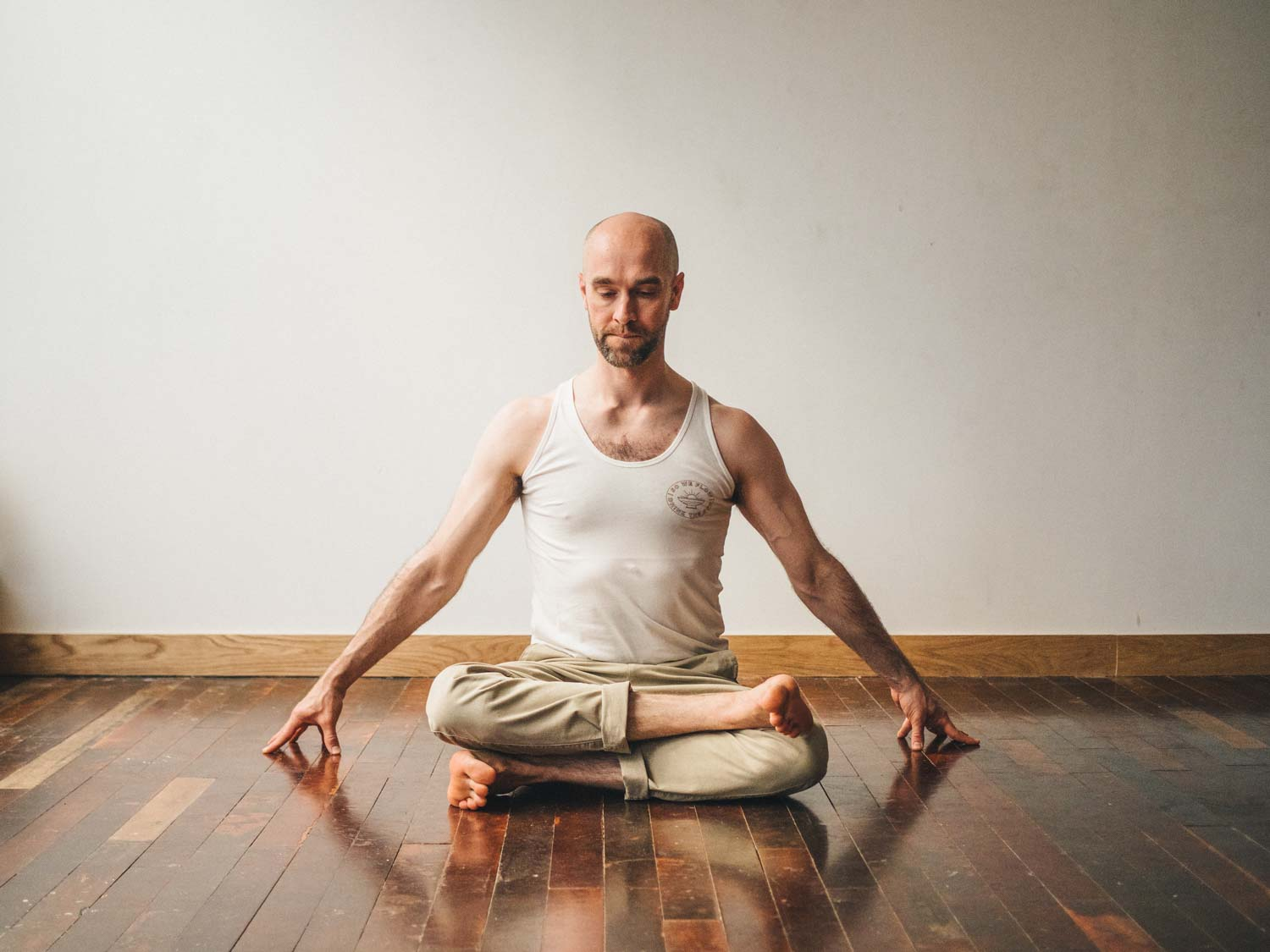 Man doing fire log pose or Agnistambhasana in yoga studio