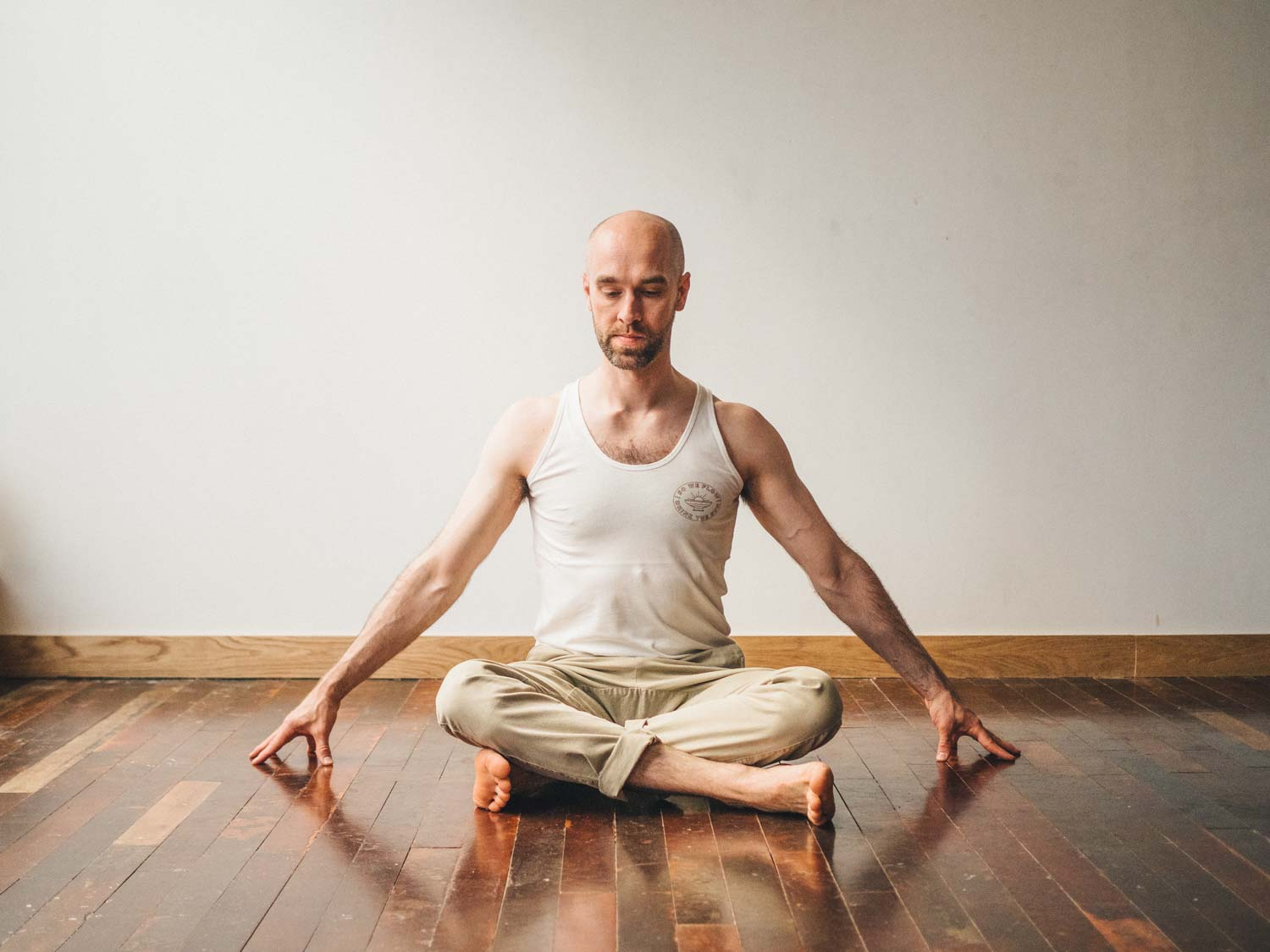 Man doing fire log pose or Agnistambhasana variation in yoga studio