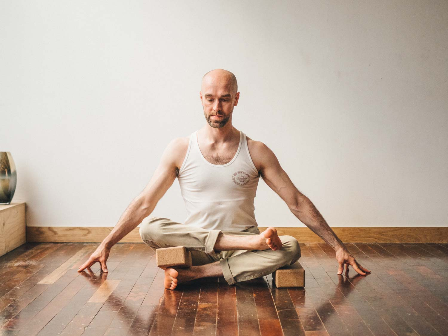 Man doing fire log pose or Agnistambhasana variation with props in yoga studio